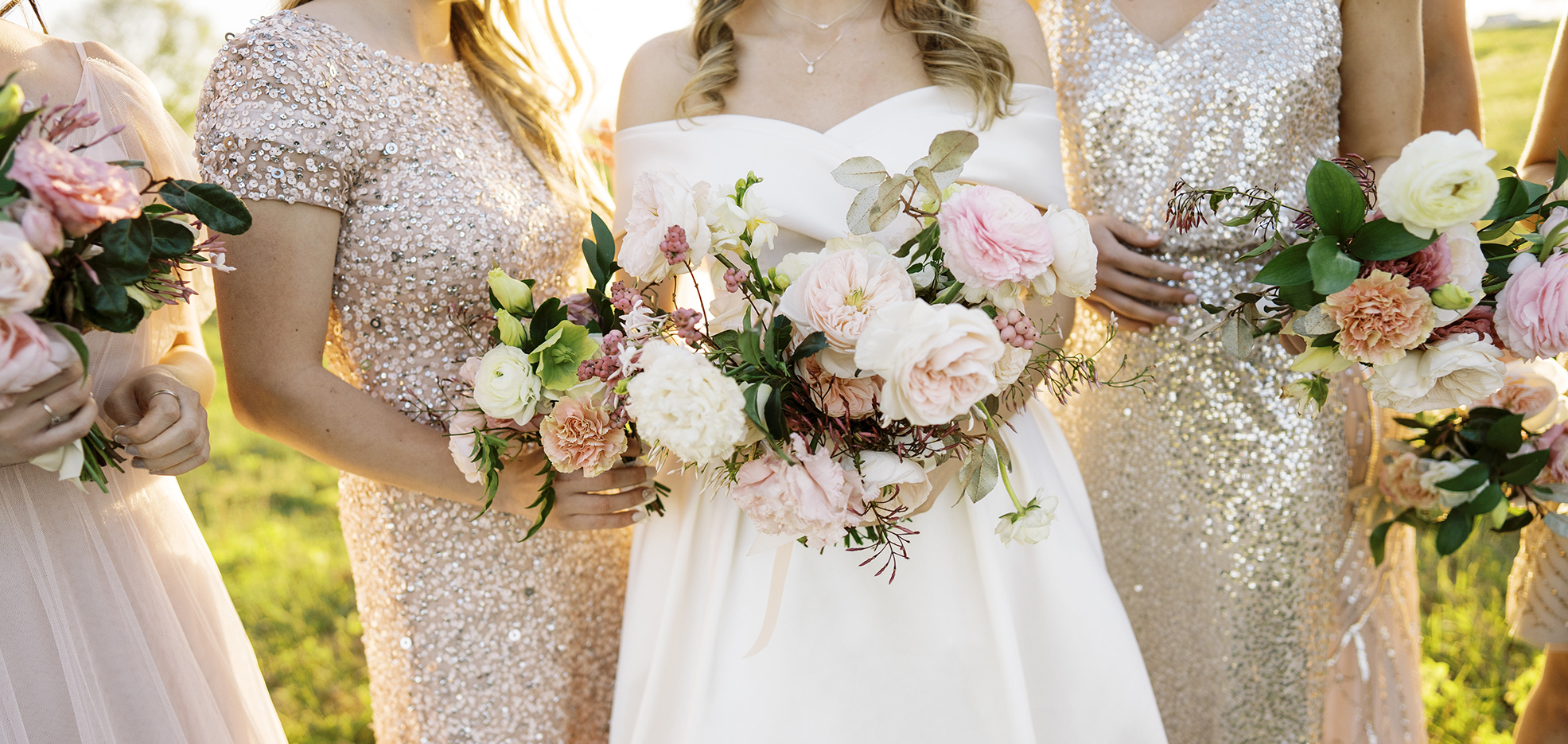 An up close photo of the bride's wedding bouquet with her bridesmaids behind her.