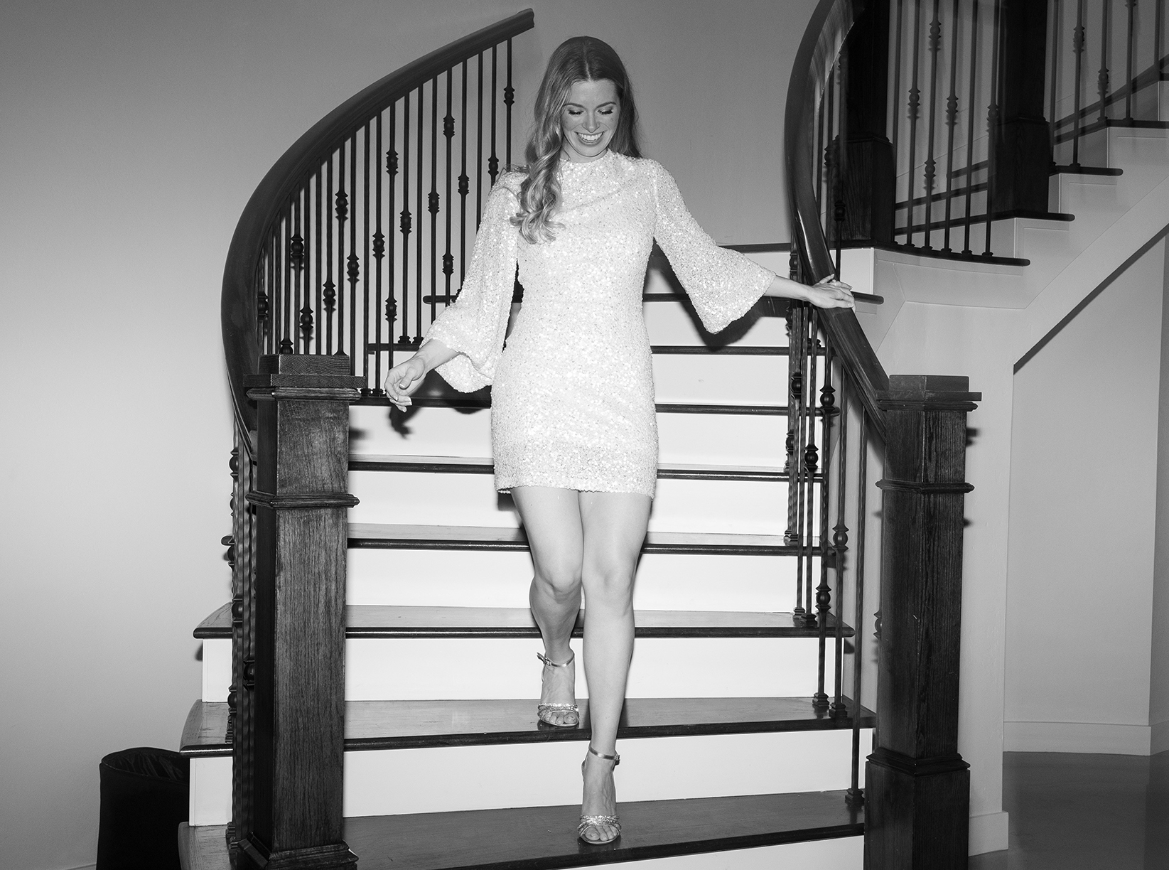 The bride walks down a spiral staircase with a shimmery white cocktail dress on.