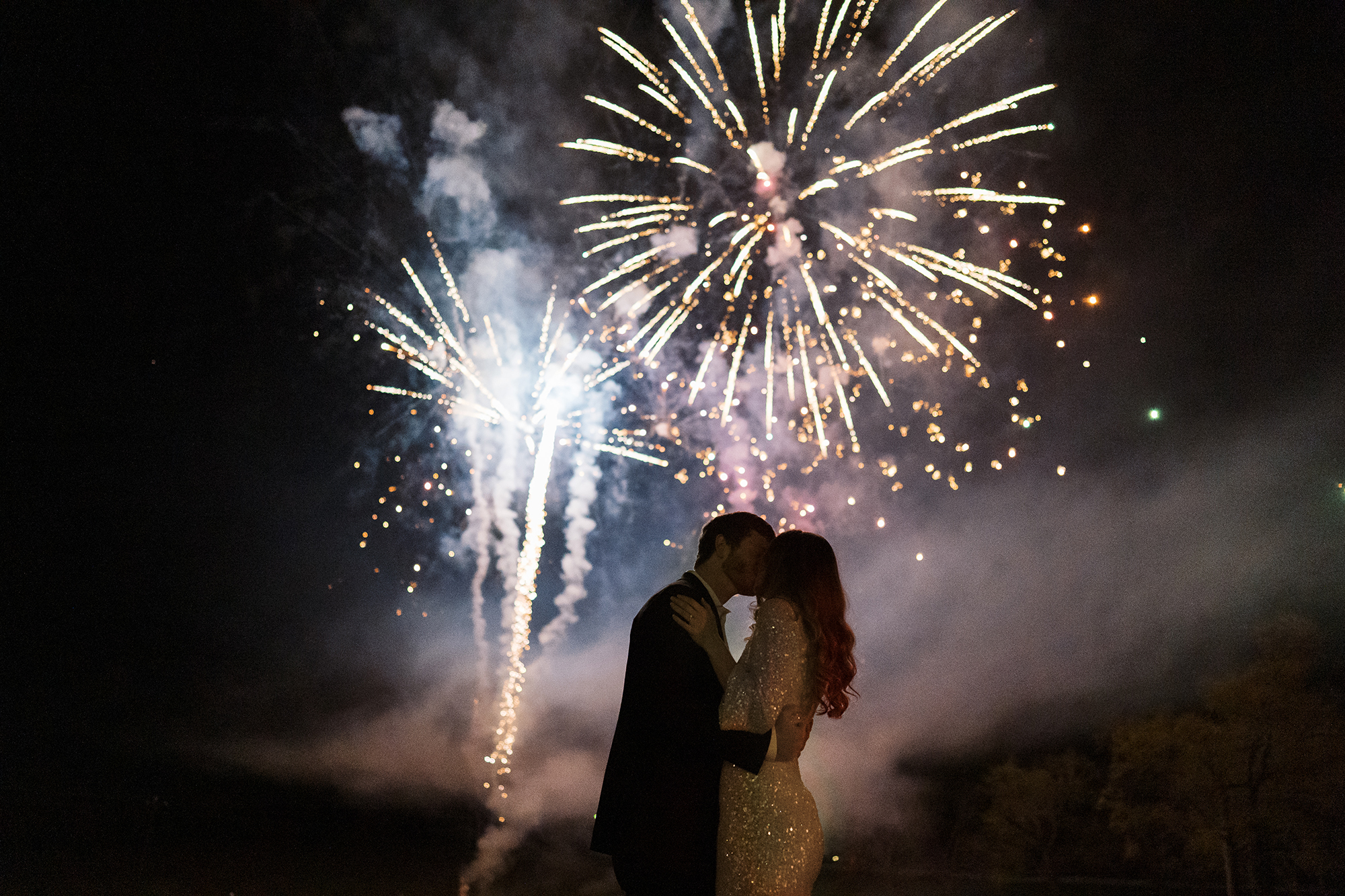 The bride and groom kiss with fireworks exploding behind them.