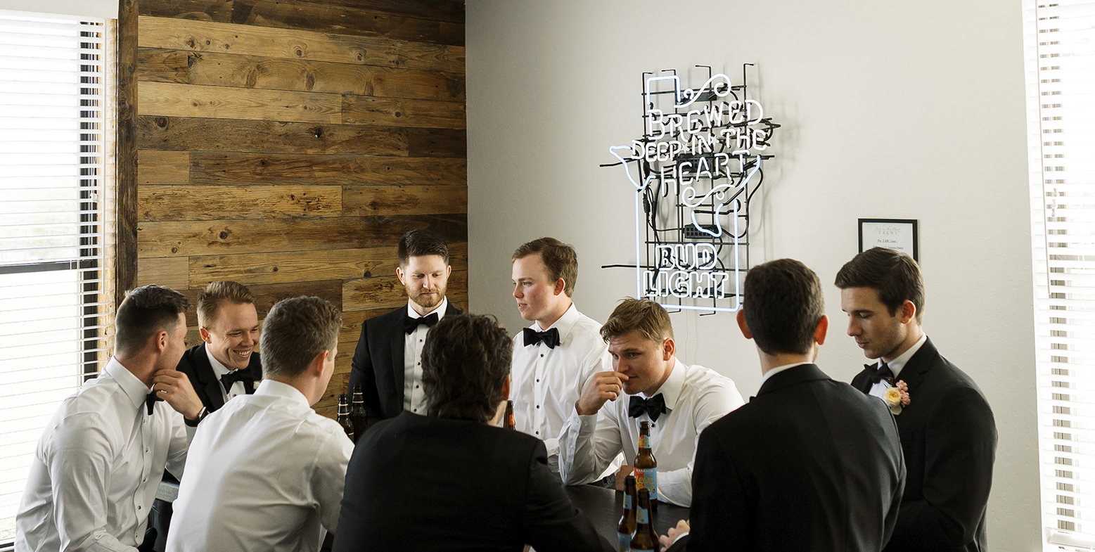 The groomsmen and the groom are drinking beers in the groom's suite.