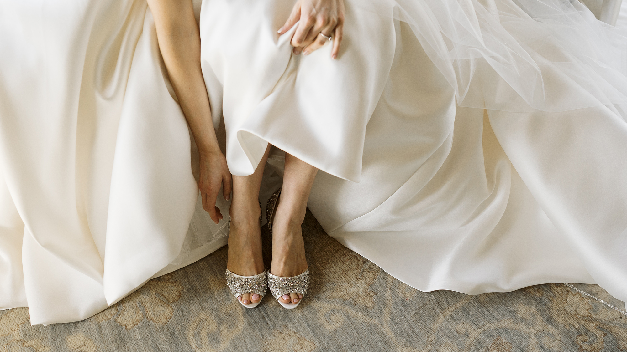 The bride puts on her wedding shoes to get ready for her timeless and airy wedding at Deep in the Heart Farms.