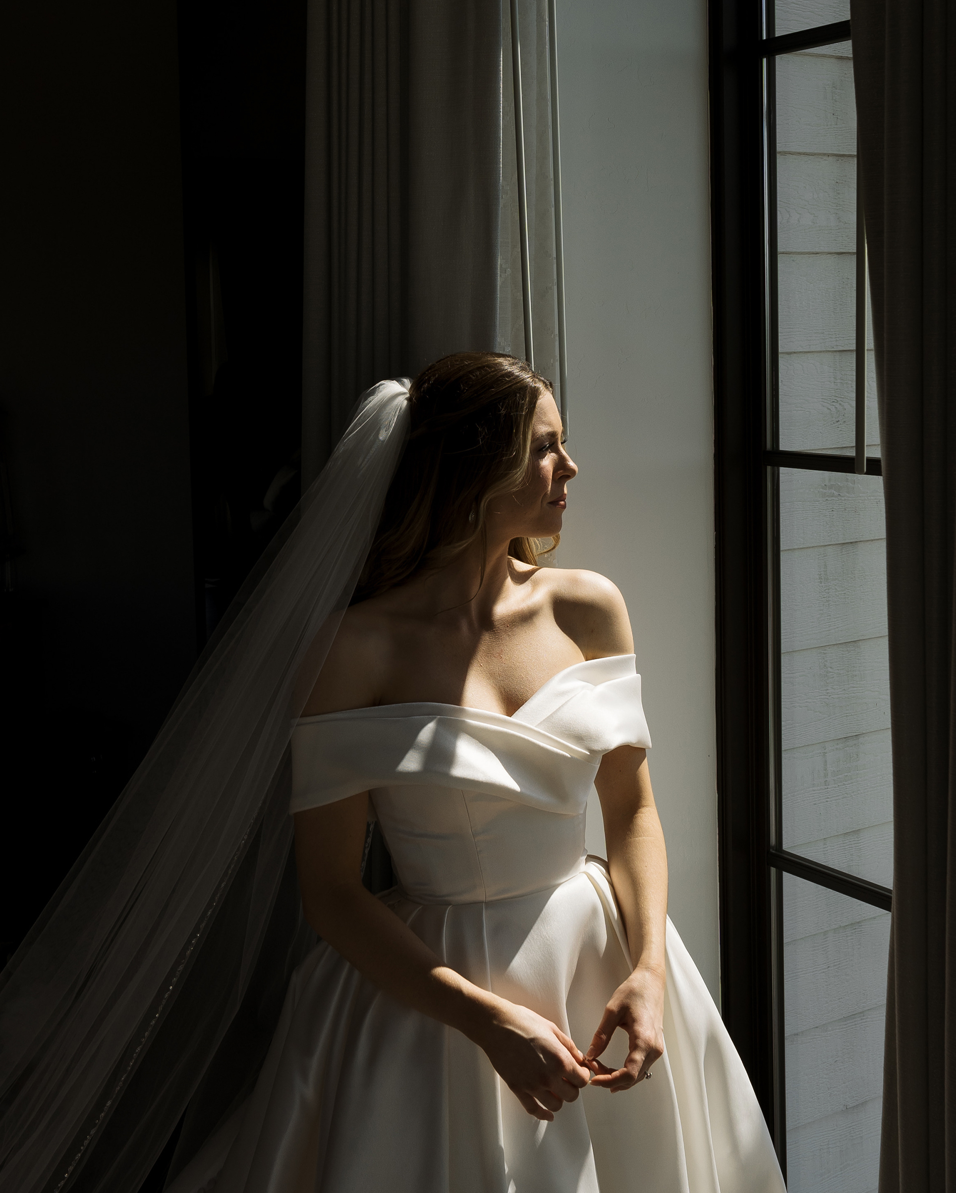 The bride is looking out the window in her wedding gown.