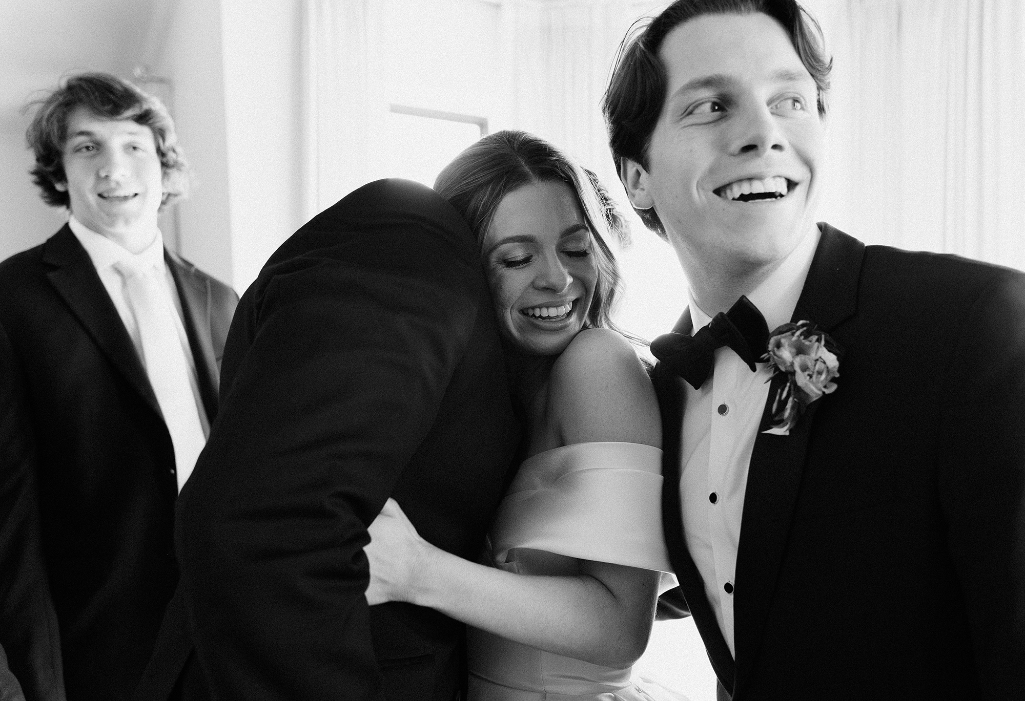 The brides hugs one of the groomsmen and smiles.