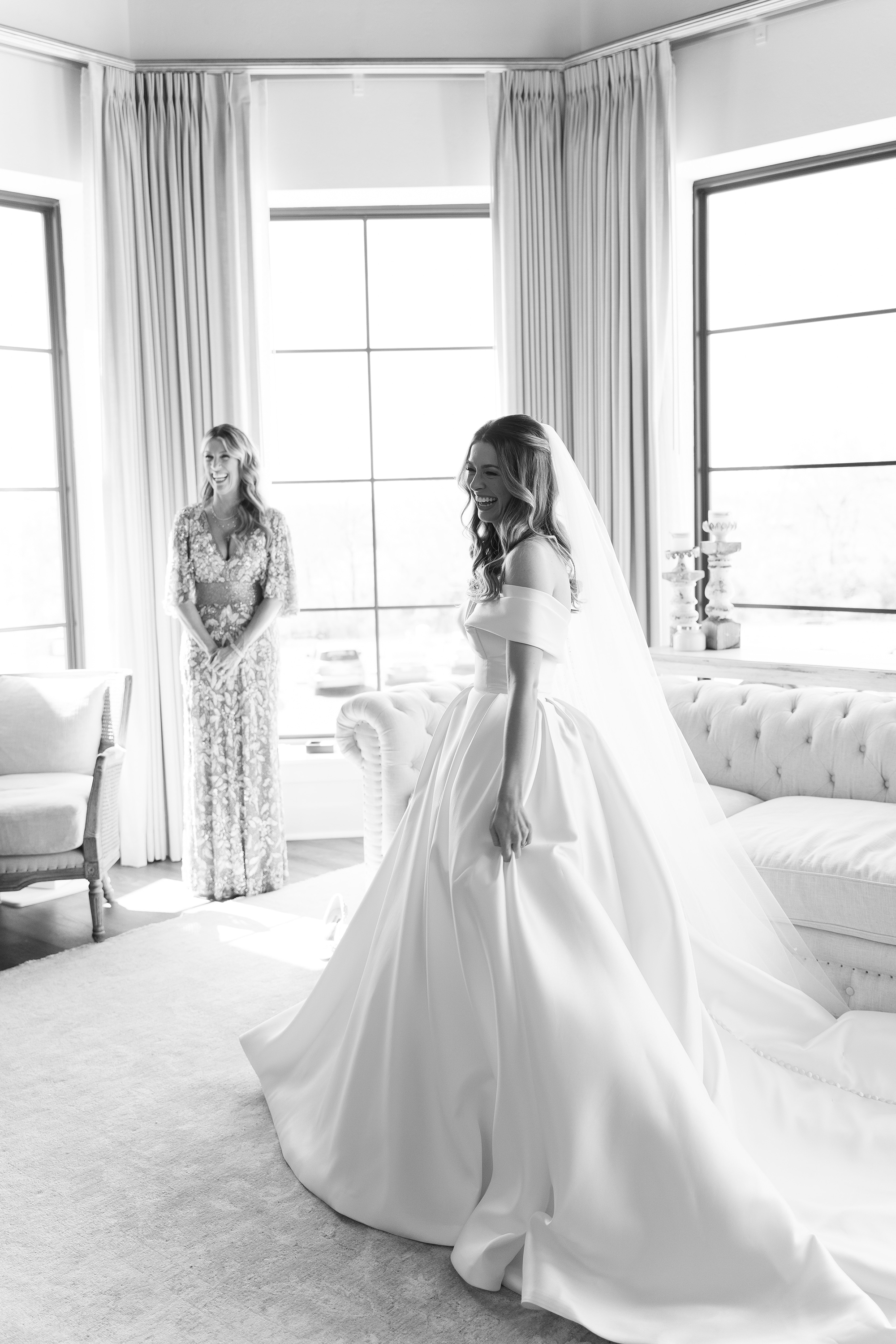 The bride smiles in her wedding dress while her mom is next to her in the bridal suite.