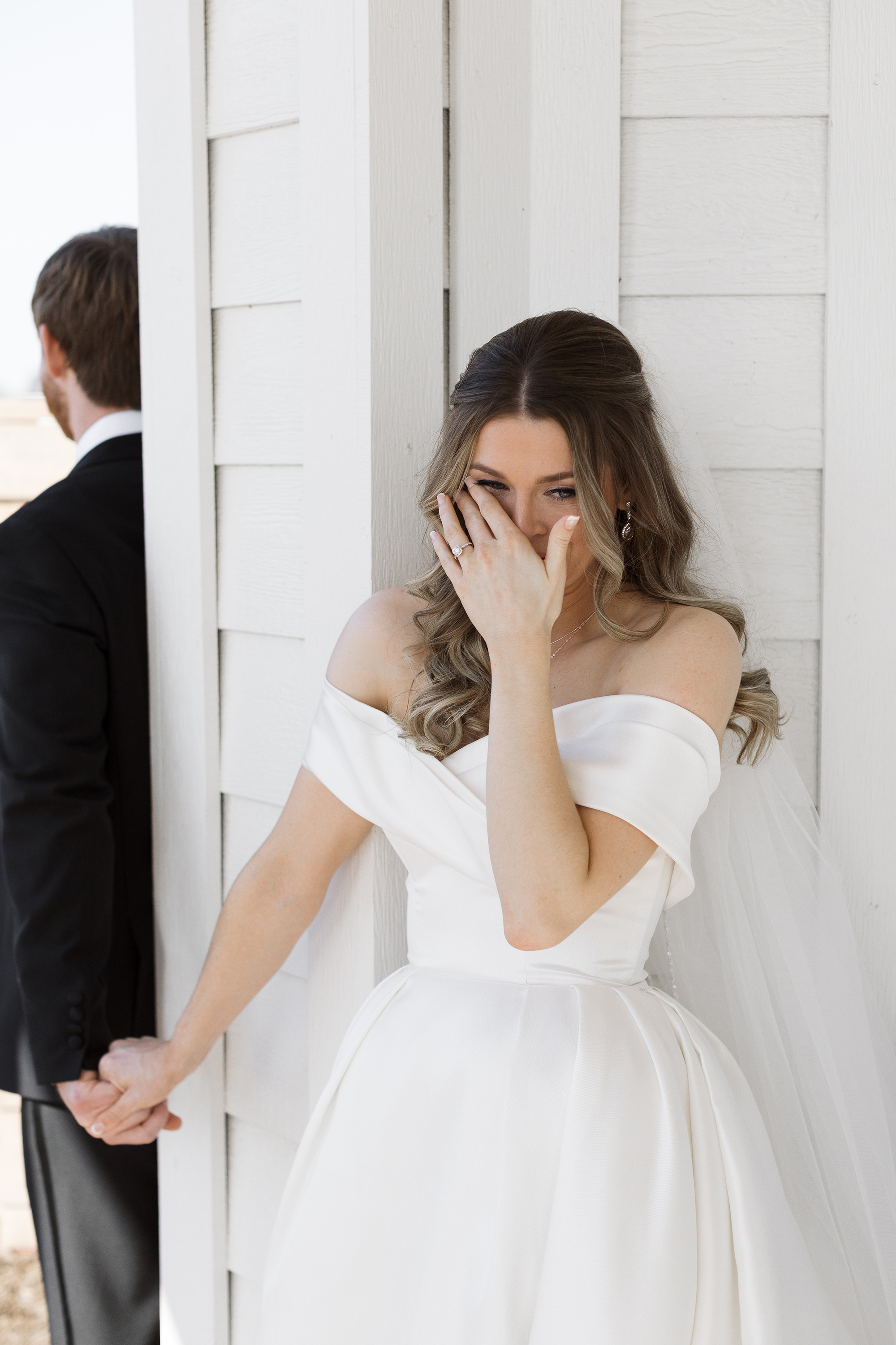 The bride and groom have their emotional first touch. The bride is wiping a tear from her eye.