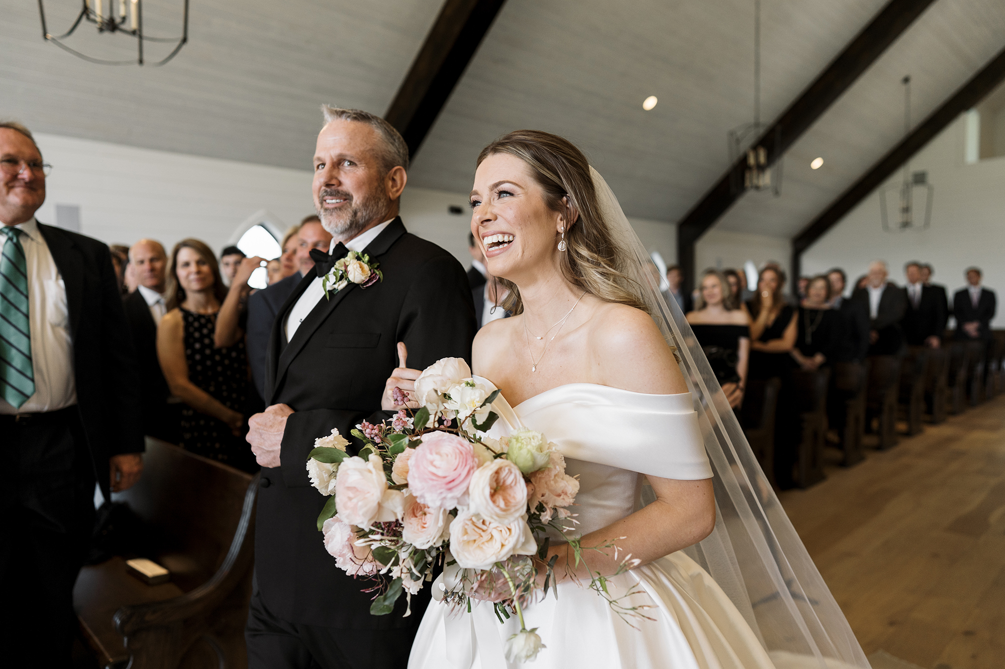 The bride is smiling while her dad walks her down the aisle at her wedding.