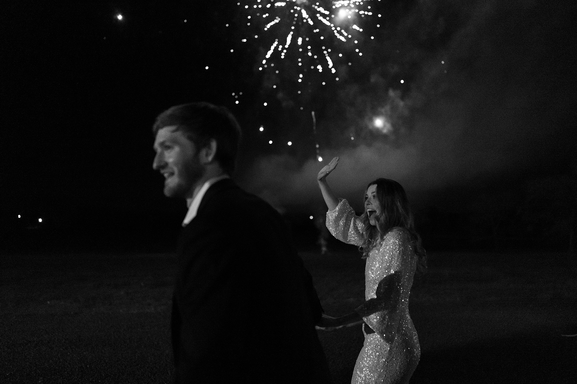 The bride and groom waving to their guests as they leave the reception with fireworks behind them.