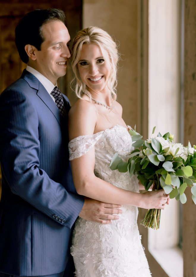 Groom in blue suit and tie holds a blonde bride in an off-the-shoulder gown after their wedding ceremony at wedding venue, The Bell Tower on 34th, in Houston, Texas.