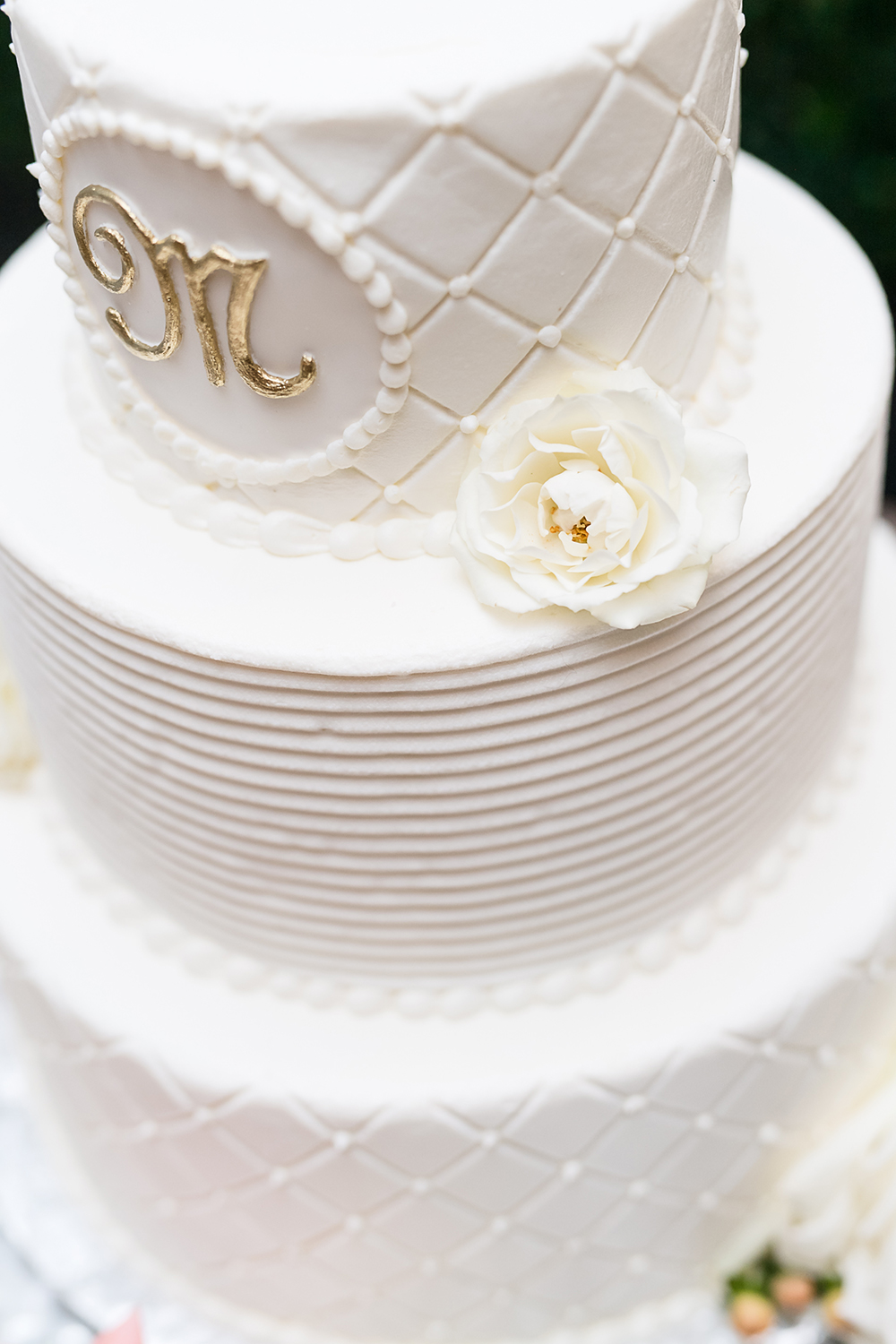 white tier wedding cake with gold lettering