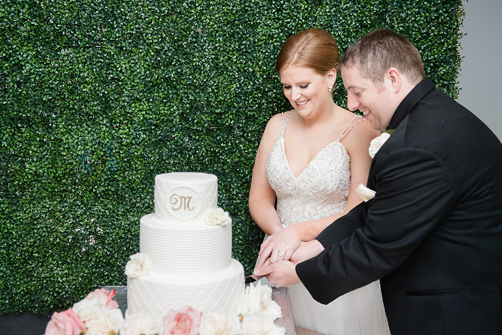 cake cutting with ivy wall background, wedding photography at ballroom reception