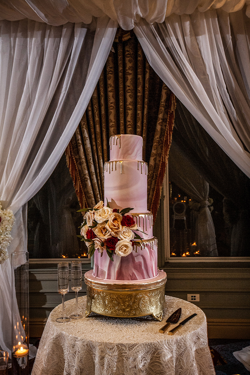 pink and white wedding cake on gold cake stand