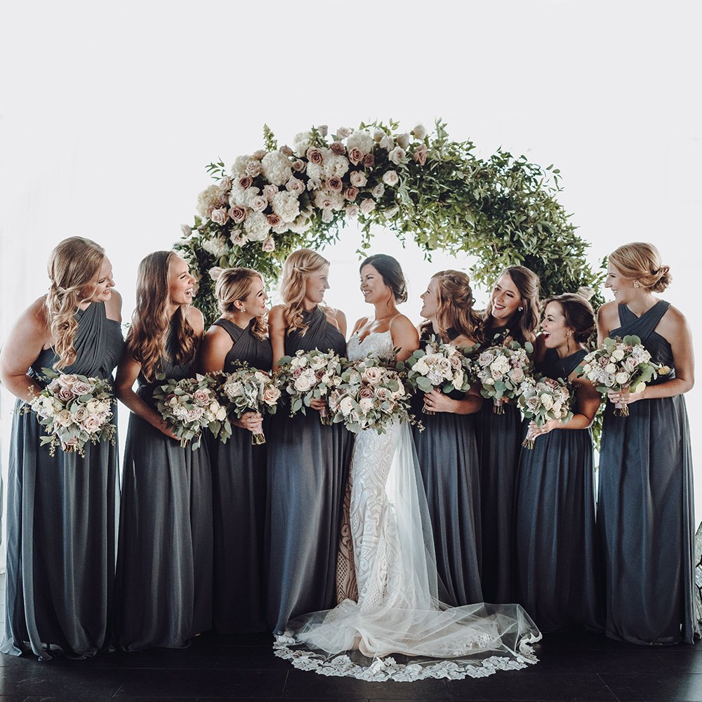 bridesmaids with bouquets in front of floral hoop