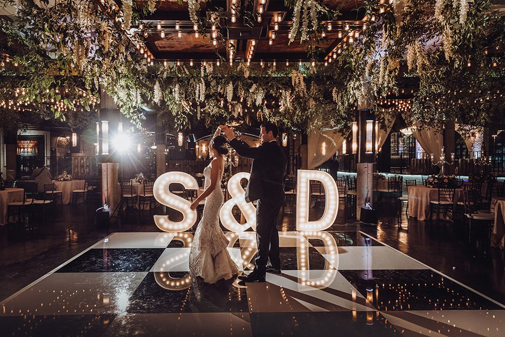 first dance at wedding reception with floral ceiling
